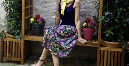 woman laying on o bench and wearing a floral print silk skirt